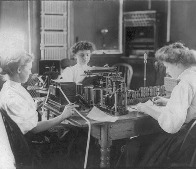 Library of Congress image. Photograph shows three women working together in an office; one operating the teletypewriter, the other writing, and another handling the receiving tape.